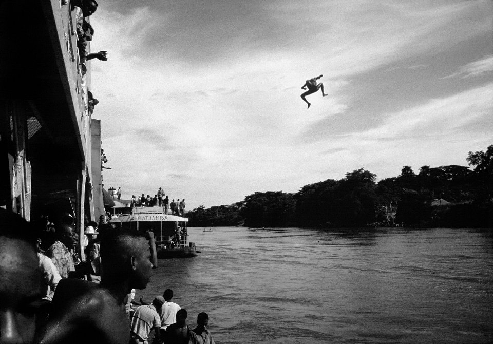 Traders, having boarded a Congo River steamer, the Colonel Kokolo, on its way to Kinshasa from Kisangani, jump off the bridge to join their colleagues for the paddle back upstream to their villages, Congo, (then Zaire), 1996